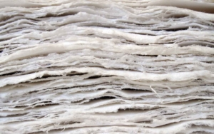 a textural image show a stack of new paper with raw edges