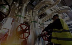 man turning valve on pipe